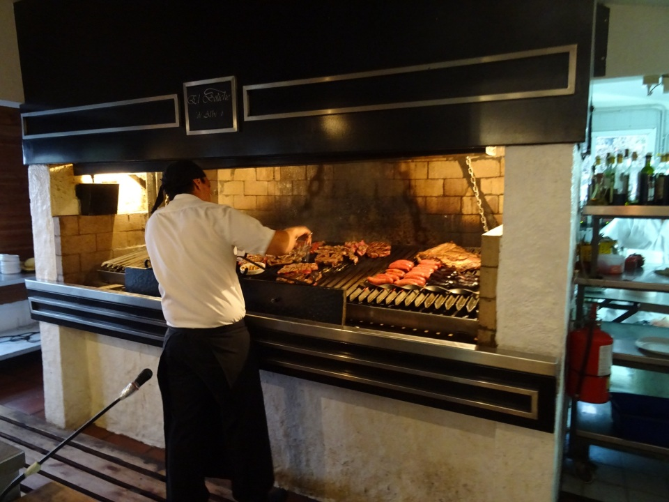 A chef at a Parilla cooking meat over a wood fire